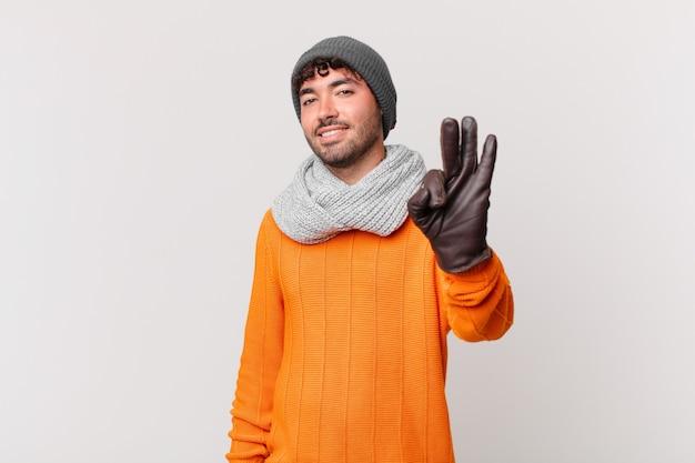 Spaanse man lacht en ziet er vriendelijk uit, toont nummer drie of derde met hand naar voren, aftellend