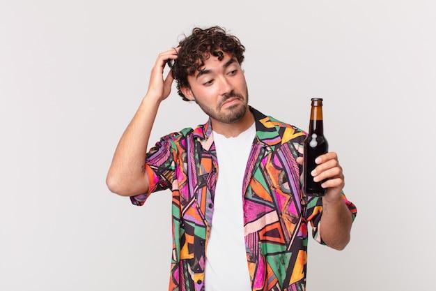 Spaanse man met bier die zich verbaasd en verward voelt, hoofd krabt en opzij kijkt