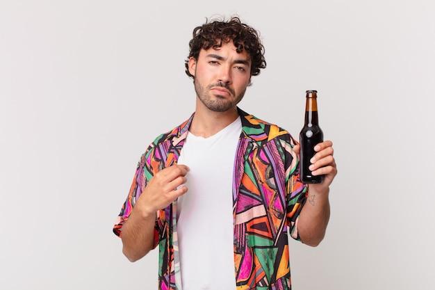 Spaanse man met bier op zoek arrogant, succesvol, positief en trots, wijzend naar zichzelf