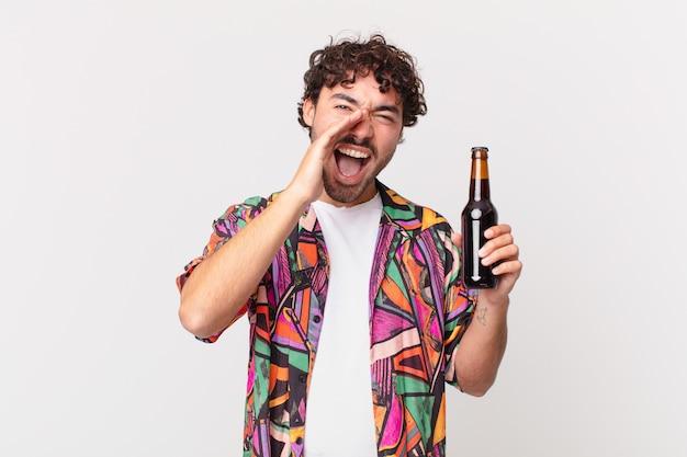 Spaanse man met bier voelt zich blij, opgewonden en positief, geeft een grote schreeuw met handen naast de mond, roept