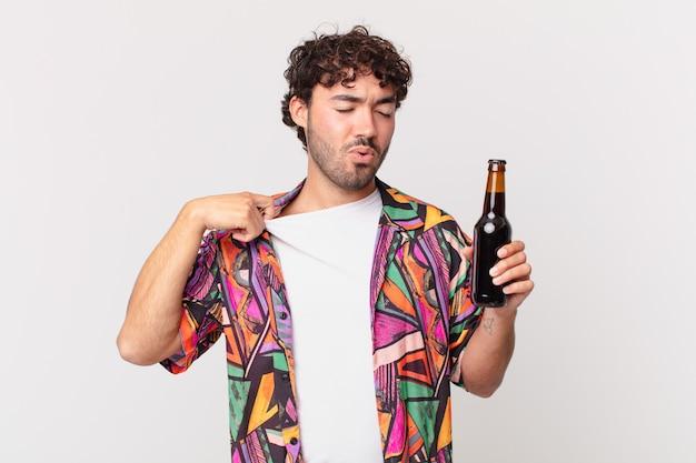 Spaanse man met bier voelt zich gestrest, angstig, moe en gefrustreerd, trekt de hals van het shirt aan en kijkt gefrustreerd door het probleem