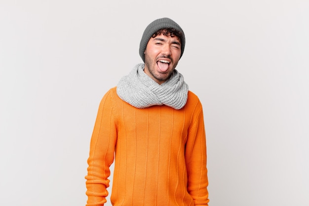 Spaanse man met vrolijke, zorgeloze, rebelse houding, grappen maken en tong uitsteken, plezier maken Premium Foto
