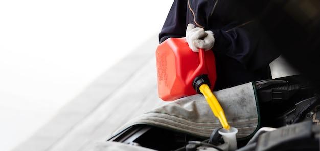 Spaanse mechanische vrouw die water vult aan autoradiator. automonteur werken in garage