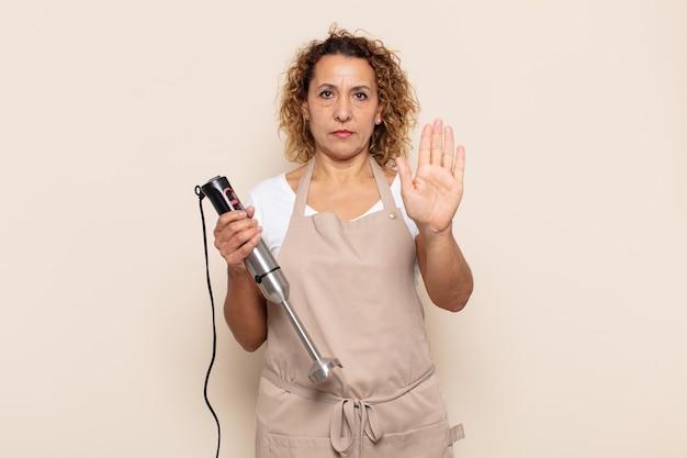 Spaanse middelbare leeftijd vrouw die ernstig, streng, ontevreden en boos kijkt die open palm toont die stopgebaar maakt