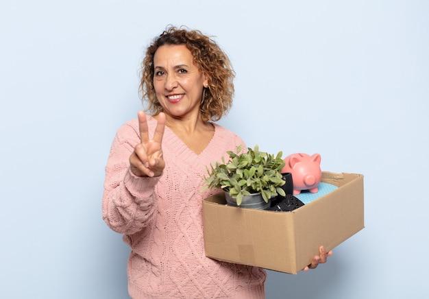 Spaanse middelbare leeftijdsvrouw die en gelukkig, zorgeloos en positief glimlacht kijkt, gebaren overwinning of vrede met één hand