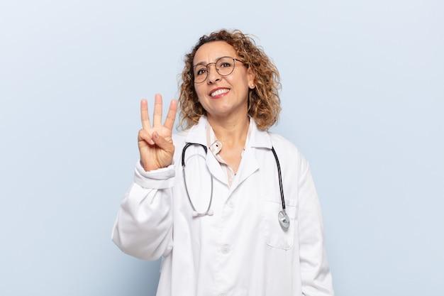 Spaanse middelbare leeftijdsvrouw die en vriendschappelijk glimlacht kijkt, nummer drie of derde met vooruit hand toont, aftellend