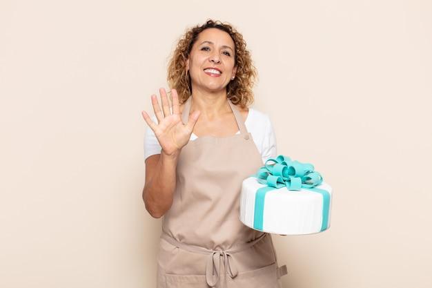 Spaanse middelbare leeftijdsvrouw die en vriendschappelijk glimlacht kijkt, nummer vijf of vijfde met vooruit hand toont, aftellend