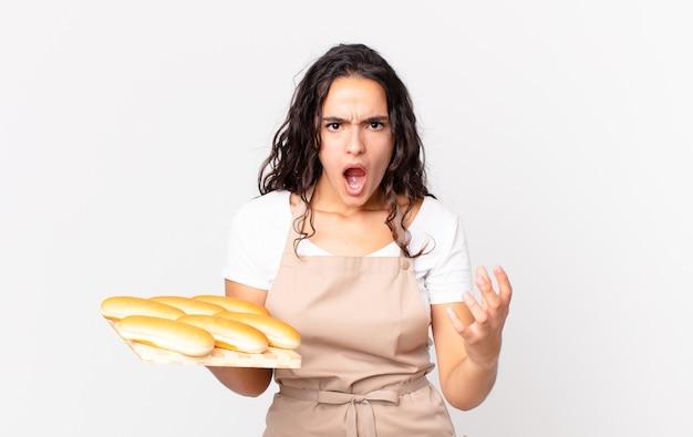 Spaanse mooie chef-kokvrouw die boos, geïrriteerd en gefrustreerd kijkt en een troy met broodbroodjes vasthoudt