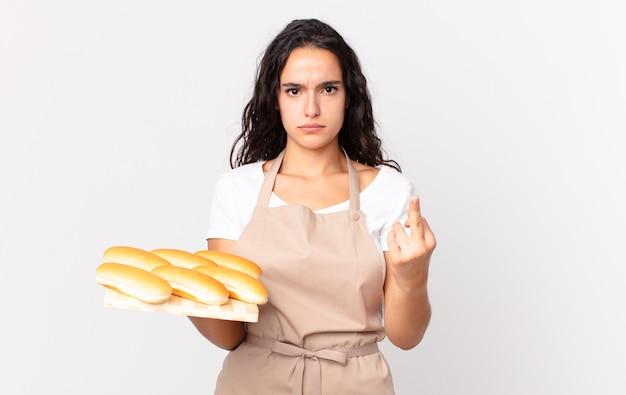 Spaanse mooie chef-kokvrouw die boos, geïrriteerd, opstandig en agressief voelt en een troy broodbroodjes vasthoudt