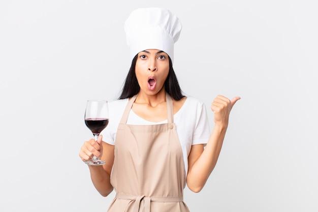 Spaanse mooie chef-kokvrouw die een glas wijn houdt