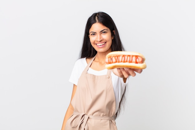 Spaanse mooie chef-kokvrouw die een hotdog houdt