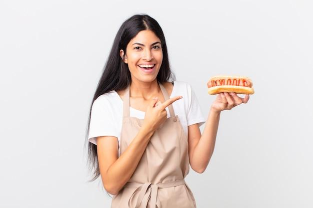 Spaanse mooie chef-kokvrouw die een hotdog houdt Premium Foto