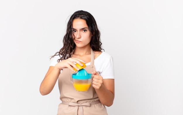 Spaanse mooie chef-kokvrouw die een jus d'orange bereidt