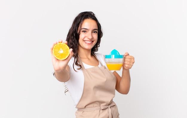 Spaanse mooie chef-kokvrouw die een jus d'orange voorbereiden Premium Foto