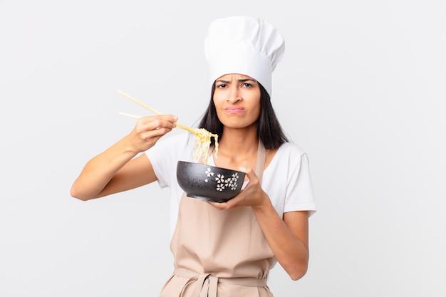 Spaanse mooie chef-kokvrouw die een noedelkom houdt