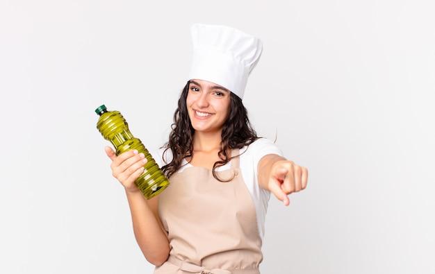 Spaanse mooie chef-kokvrouw die een olijfoliefles houdt