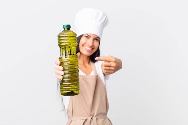 Spaanse mooie chef-kokvrouw die een olijfoliefles houdt.