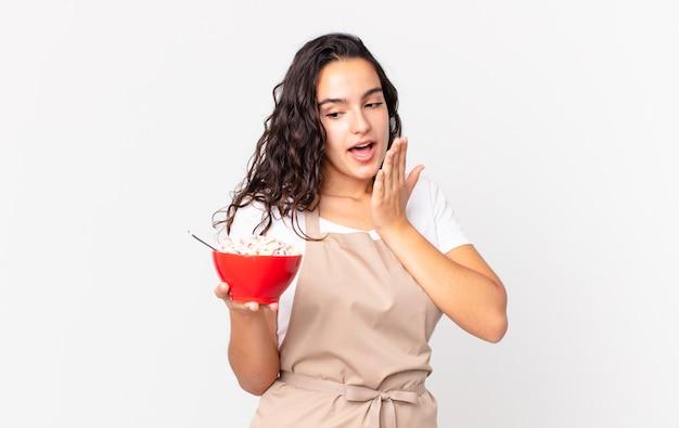 Spaanse mooie chef-kokvrouw die een ontbijtkom met melk houdt