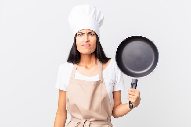 Spaanse mooie chef-kokvrouw die een pan houdt