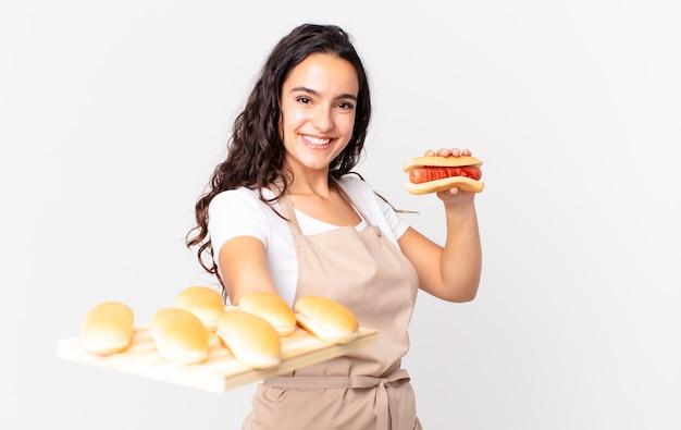 Spaanse mooie chef-kokvrouw die een troy broodbroodjes houdt