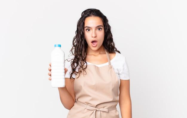 Spaanse mooie chef-kokvrouw die erg geschokt of verrast kijkt en een melkfles vasthoudt