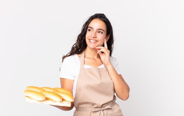 Spaanse mooie chef-kokvrouw die gelukkig glimlacht en dagdroomt of twijfelt en een troy met broodbroodjes vasthoudt