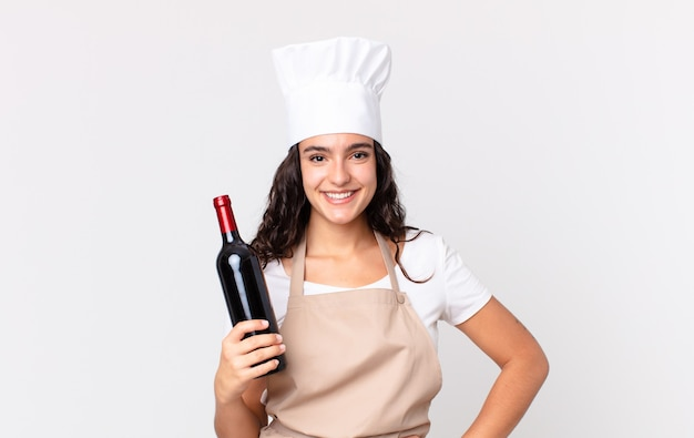 Spaanse mooie chef-kokvrouw die gelukkig glimlacht met een hand op de heup en zelfverzekerd en een wijnfles vasthoudt