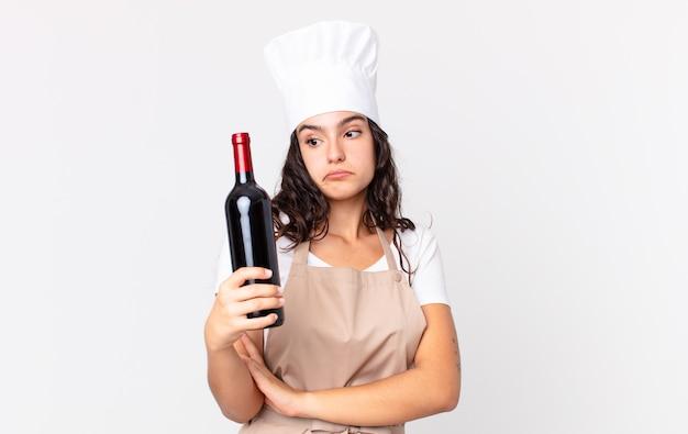 Spaanse mooie chef-kokvrouw die haar schouders ophaalt, zich verward en onzeker voelt en een wijnfles vasthoudt