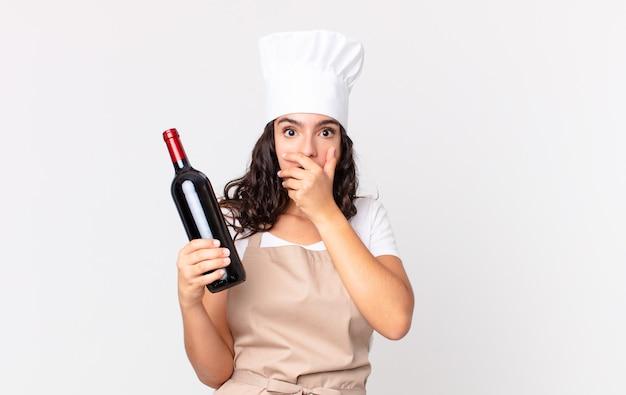 Spaanse mooie chef-kokvrouw die mond bedekt met handen met een geschokte en een wijnfles vasthoudt