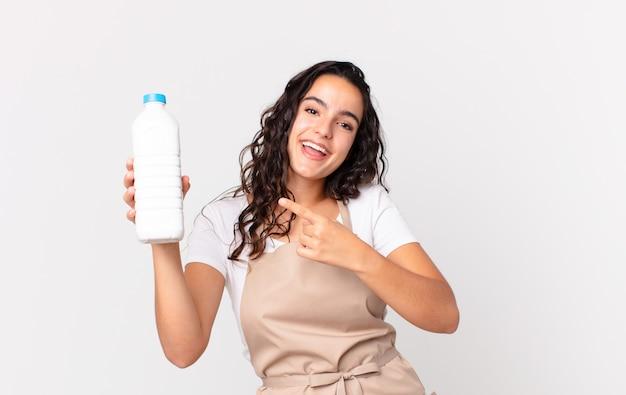 Spaanse mooie chef-kokvrouw die opgewonden en verrast kijkt en naar de zijkant wijst en een melkfles vasthoudt