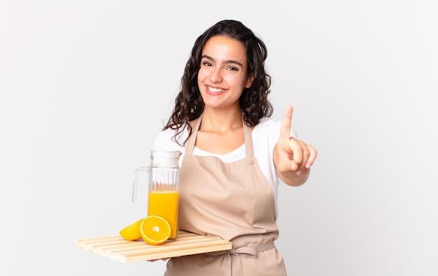 Spaanse mooie chef-kokvrouw die trots en zelfverzekerd glimlacht en nummer één maakt en een sinaasappelsap vasthoudt