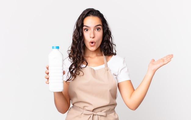 Spaanse mooie chef-kokvrouw die verrast en geschokt kijkt, met open mond terwijl ze een voorwerp vasthoudt en een melkfles vasthoudt