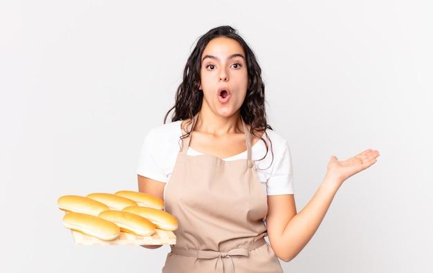 Spaanse mooie chef-kokvrouw die verrast en geschokt kijkt, met open mond terwijl ze een voorwerp vasthoudt en een troy met broodbroodjes vasthoudt