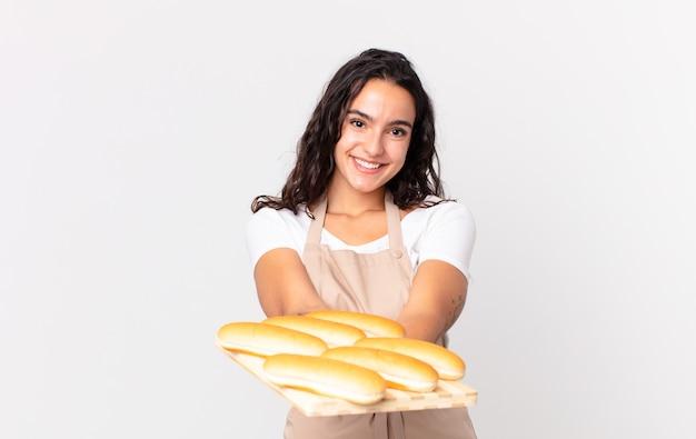 Spaanse mooie chef-kokvrouw die vrolijk glimlacht met vriendelijk en een concept aanbiedt en toont en een troy met broodbroodjes vasthoudt