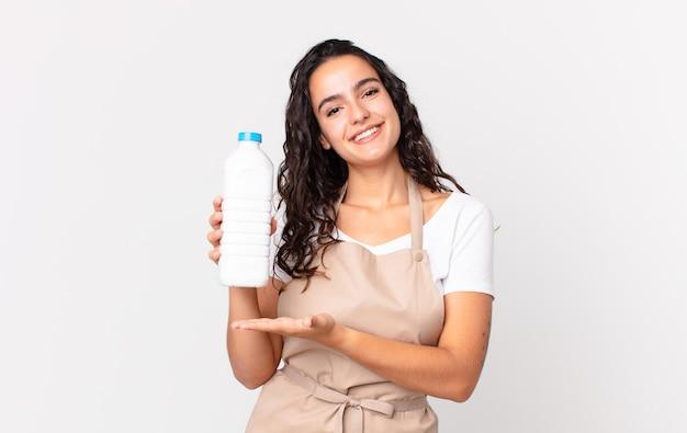 Spaanse mooie chef-kokvrouw die vrolijk lacht, zich gelukkig voelt en een concept toont en een melkfles vasthoudt