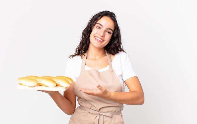 Spaanse mooie chef-kokvrouw die vrolijk lacht, zich gelukkig voelt en een concept toont en een troy met broodbroodjes vasthoudt