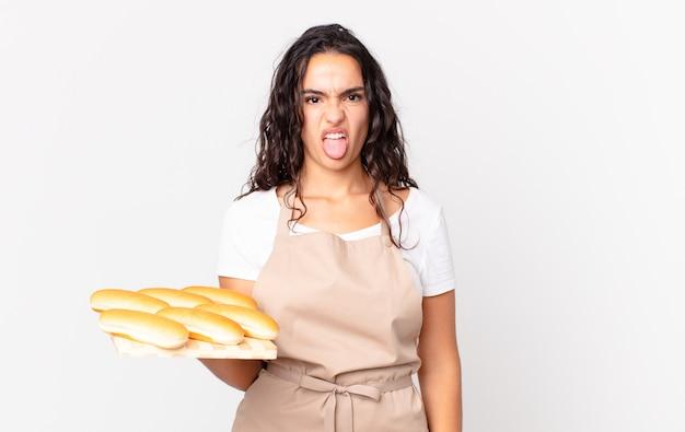 Spaanse mooie chef-kokvrouw die walgt en geïrriteerd voelt en tong uitsteekt en een troy met broodbroodjes vasthoudt