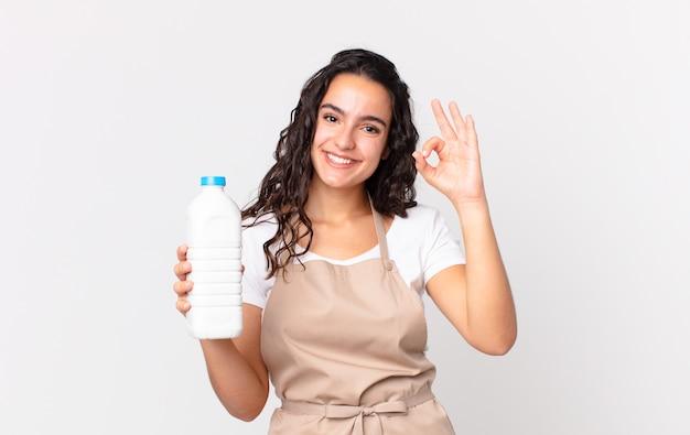 Spaanse mooie chef-kokvrouw die zich gelukkig voelt, goedkeuring toont met een goed gebaar en een melkfles vasthoudt