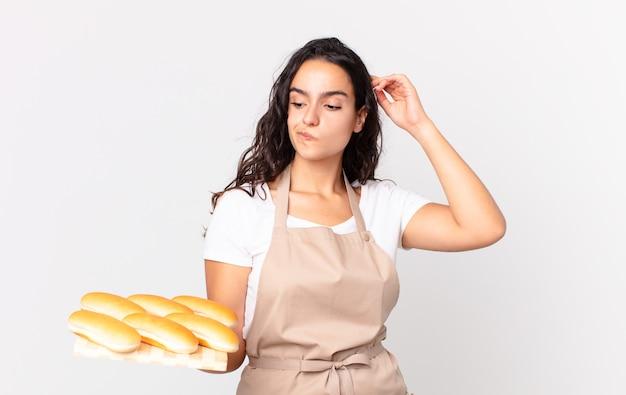 Spaanse mooie chef-kokvrouw die zich verbaasd en verward voelt, hoofd krabt en een troy met broodbroodjes vasthoudt
