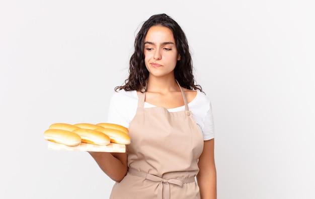 Spaanse mooie chef-kokvrouw die zich verdrietig, overstuur of boos voelt en opzij kijkt en een troy met broodbroodjes vasthoudt