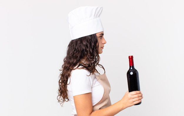 Spaanse mooie chef-kokvrouw op profielaanzicht denkend, verbeeldend of dagdromen en een wijnfles vasthouden