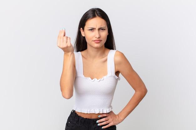 Spaanse mooie vrouw die capice of geldgebaar maakt en zegt dat je moet betalen