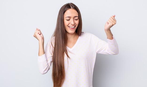 Spaanse mooie vrouw die er buitengewoon blij en verrast uitziet, succes viert, schreeuwt en springt