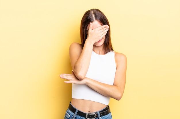 Spaanse mooie vrouw die er gestrest, beschaamd of overstuur uitziet, met hoofdpijn, gezicht bedekt met hand