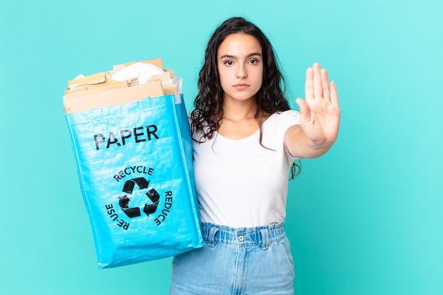 Spaanse mooie vrouw die er serieus uitziet met een open palm die een stopgebaar maakt en een gerecyclede papieren zak vasthoudt