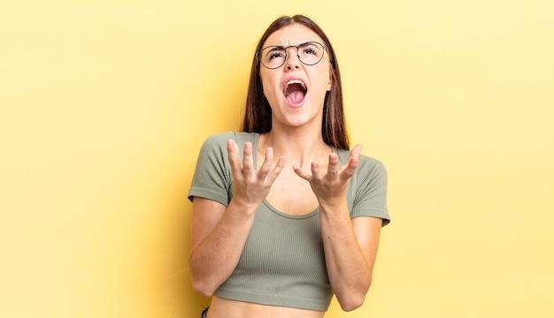 Spaanse mooie vrouw die er wanhopig en gefrustreerd, gestrest, ongelukkig en geïrriteerd uitziet, schreeuwend en schreeuwend