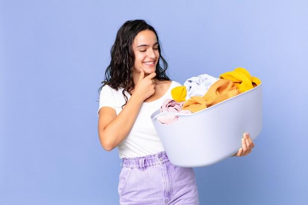Spaanse mooie vrouw die lacht met een gelukkige, zelfverzekerde uitdrukking met de hand op de kin en een wasmand vasthoudt