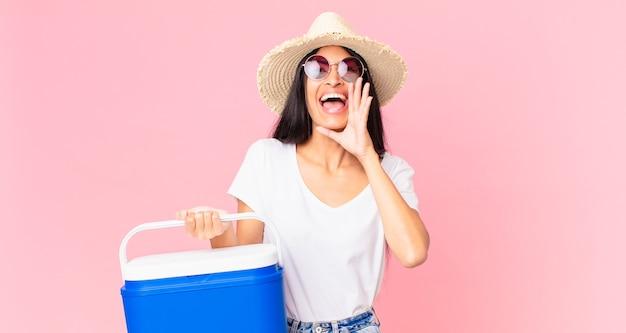 Spaanse mooie vrouw die zich gelukkig voelt, een grote schreeuw geeft met de handen naast de mond met een draagbare picknickkoelkast