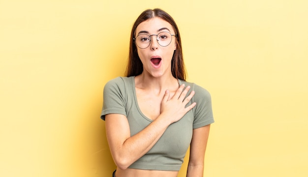 Spaanse mooie vrouw die zich geschokt en verrast voelt, glimlacht, hand ter harte neemt, blij is om degene te zijn of dankbaarheid toont