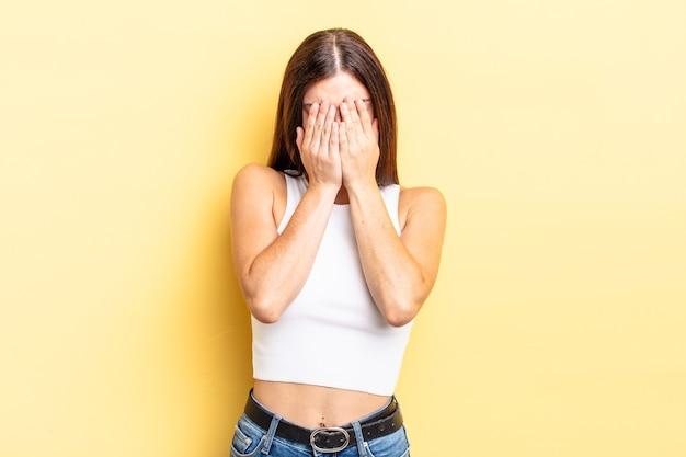 Spaanse mooie vrouw die zich verdrietig, gefrustreerd, nerveus en depressief voelt, haar gezicht met beide handen bedekt, huilt